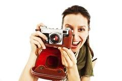 Aufgeregte junge Frau, die ein Foto mit Kamera macht Lizenzfreie Stockbilder