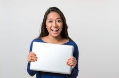 Aufgeregte junge Frau, die einen silbernen Laptop hält stockfotos