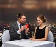 Aufgeregte junge Frau, die Freund mit Kasten betrachtet Lizenzfreie Stockfotografie