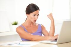 Aufgeregte junge Frau, die an Laptop sitzt und arbeitet Lizenzfreie Stockbilder