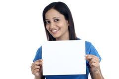 Aufgeregte junge Frau, die leere weiße Karte zeigt Stockfotos