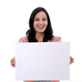 Aufgeregte junge Frau, die leeren weißen Vorstand anhält Stockfotos