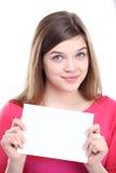 Aufgeregte junge Frau, die leeres leeres Papier zeigt Lizenzfreie Stockfotografie