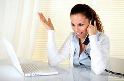 Aufgeregte junge Frau, die am Telefon spricht Stockfotos