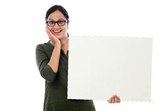 Aufgeregte junge Frau, die weißes Brett hält Lizenzfreie Stockfotografie