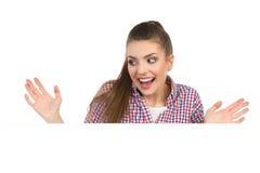 Aufgeregte junge Frau hinter weißer Fahne Stockfotos