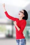 Aufgeregte junge Frau mit den Fäusten oben Stockfoto