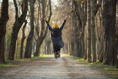Aufgeregte junge Frau springt mit den Armen, die oben angehoben werden lizenzfreies stockbild