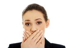 Aufgeregte junge Geschäftsfrau, die ihren Mund bedeckt stockfotografie