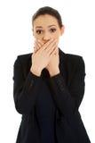 Aufgeregte junge Geschäftsfrau, die ihren Mund bedeckt Lizenzfreies Stockbild