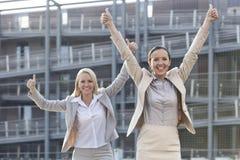 Aufgeregte junge Geschäftsfrauen, die Daumen oben gegen Bürogebäude gestikulieren Stockfoto