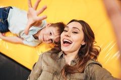 Aufgeregte junge Mutter, die mit ihrem kleinen Sohn spielt Lizenzfreie Stockfotos