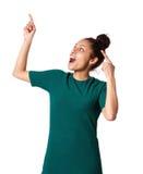 Aufgeregte junge oben zeigende und lachende Frau Stockfotografie