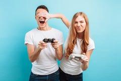 Aufgeregte junge Paare, ein Kerl und ein Mädchen, mit Steuerknüppeln in ihren Händen, die Videospiele auf einem blauen Hintergrun lizenzfreies stockfoto