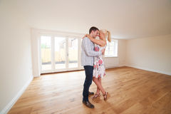 Aufgeregte junge Paare im leeren Raum des neuen Hauses Lizenzfreie Stockfotografie