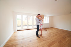 Aufgeregte junge Paare im leeren Raum von ihrem ersten Haupt Lizenzfreie Stockbilder