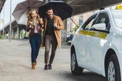 aufgeregte junge Paare mit den Regenschirmen, die zusammen zu laufen lizenzfreies stockbild