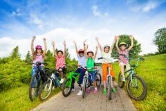 Aufgeregte Kinder in den Sturzhelmen auf Fahrrädern mit den Händen oben Stockbilder