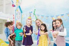 Aufgeregte Kinder, die fallende Konfettis von den Crackern betrachten lizenzfreies stockbild
