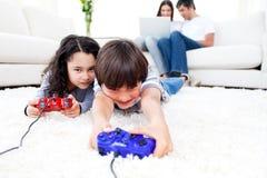 Aufgeregte Kinder, die Videospiele spielen Lizenzfreie Stockfotografie