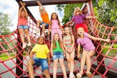 Aufgeregte Kinder, die zusammen auf Nettoseilen spielen Stockbild