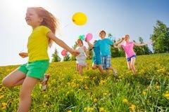 Aufgeregte Kinder mit Ballonlauf auf dem Gebiet Stockbild