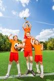 Aufgeregte Kinder mit gewonnenem Cupstand in der Pyramide Stockfoto