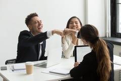 Aufgeregte Kollegen, die den Fauststoß feiert Erfolg geben lizenzfreies stockbild