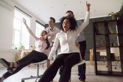 Aufgeregte Kollegen, die Spaßreitstühle während des Arbeitsbruches haben lizenzfreie stockfotos