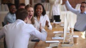Aufgeregte männliche Arbeitskraft, die gute Nachrichten mit dem glücklichen feiernden Team teilt stock video footage