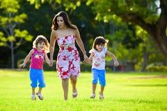 Aufgeregte Mama und zwei Töchter, die in Gras springen Stockbild