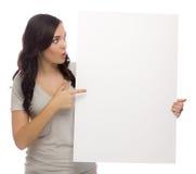 Aufgeregte Mischrasse-Frau, die leeres Zeichen auf Weiß hält Stockfoto