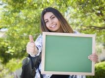 Aufgeregte Mischrasse-Studentin Holding Blank Chalkboard Stockfotografie