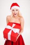Aufgeregte nette blonde junge Frau, die rotes Geschenk hält Stockbild