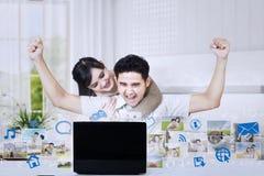 Aufgeregte Paare angehobene Arme, die Laptop betrachten Stockbilder