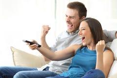 Aufgeregte Paare, die auf Couch fernsehen stockbilder