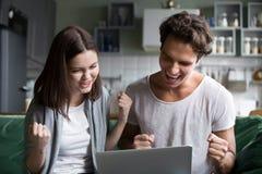 Aufgeregte Paare ekstatisch durch den on-line-Gewinn, der Laptopschirm betrachtet stockfoto