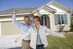 Aufgeregte Paare in Front Of New House Lizenzfreies Stockfoto