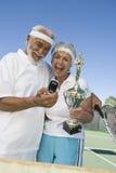 Aufgeregte Paare mit der Trophäe, die Selbstporträt am Tennisplatz nimmt Stockfotografie