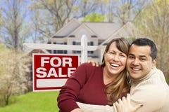 Aufgeregte Paare vor für Verkaufs-Zeichen und Haus Lizenzfreie Stockbilder