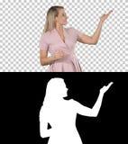 Aufgeregte schöne junge Frau im rosa Kleid sprechend mit Kamera, Alpha Channel stockfoto
