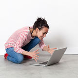 Aufgeregte schöne junge Frau, die auf Laptop auf dem Boden in Verbindung steht Lizenzfreie Stockbilder