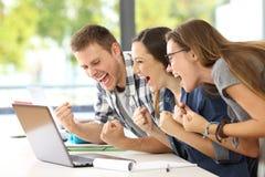 Aufgeregte Studenten, die gute Nachrichten in einem Klassenzimmer lesen lizenzfreie stockfotos