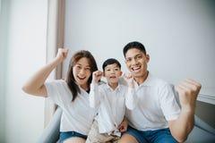 Aufgeregte und glückliche Familie mit den Armen beim Aufpassen von televis angehoben lizenzfreie stockfotografie