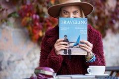 Aufgeregte Zeitschrift der jungen Frau Leseüber Reisen Stockfotos