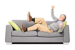 Aufgeregter älterer Mann gesetzt auf einer hörenden Musik des Sofas Stockfotografie