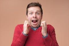 Aufgeregter überraschter junger Mann in der roten Strickjacke, die Gesichter athis der geballten Fäuste, entsetzt hält lizenzfreie stockfotografie