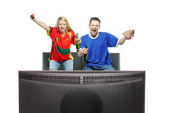 Aufgeregter überwachender Sport des Mannes und der Frau auf einem Fernsehapparat Stockfotos