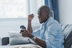 aufgeregter Afroamerikanermann, der Videospiel mit Steuerknüppel spielt lizenzfreies stockbild