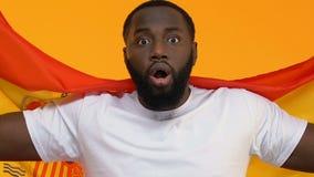 Aufgeregter afroer-amerikanisch Mann, der die spanische Flagge, wurzelnd für Lieblingssportteam hält stock video